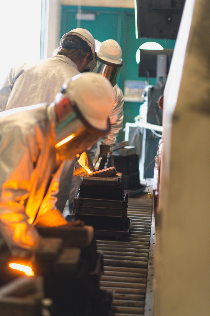 As the pouring team fills the 3rd mold [middle ground], an MSE staff member [foreground] lifts the mold jacket from the 2nd mold, and will transfer it to the waiting 4th mold [background] prior to it being poured. The jacket supports the green sand mold against the hydraulic pressure of the liquid metal entering the mold.
