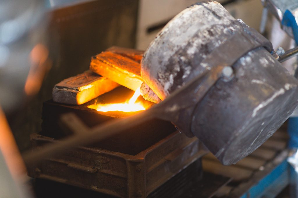 The pouring basin is kept full so that the molten metal quickly fills the mold cavity.