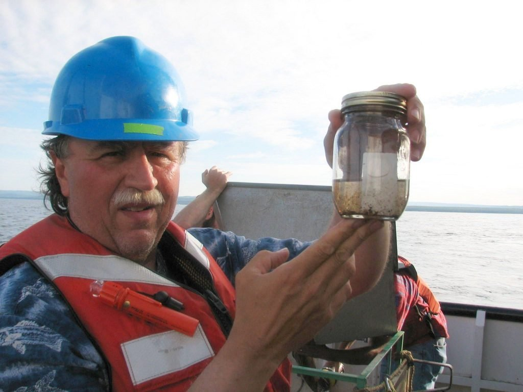 Dr. Martin Auer, Michigan Tech Civil and Environmental Engineering Professor Emeritus hold us a test capsule on board a research vessel on Lake Superior
