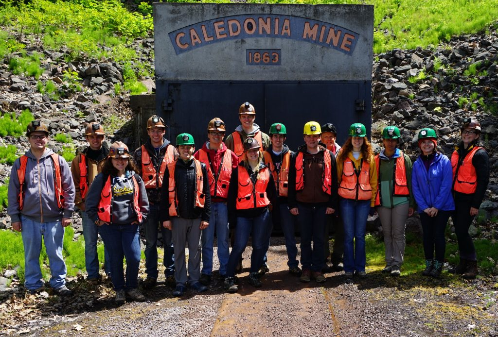 A class of 14 Michigan Tech field geology students stand at the entrance of the Caledonia Mine, Ontonagon County, Michigan. Photo courtesy of Steve Chittick.