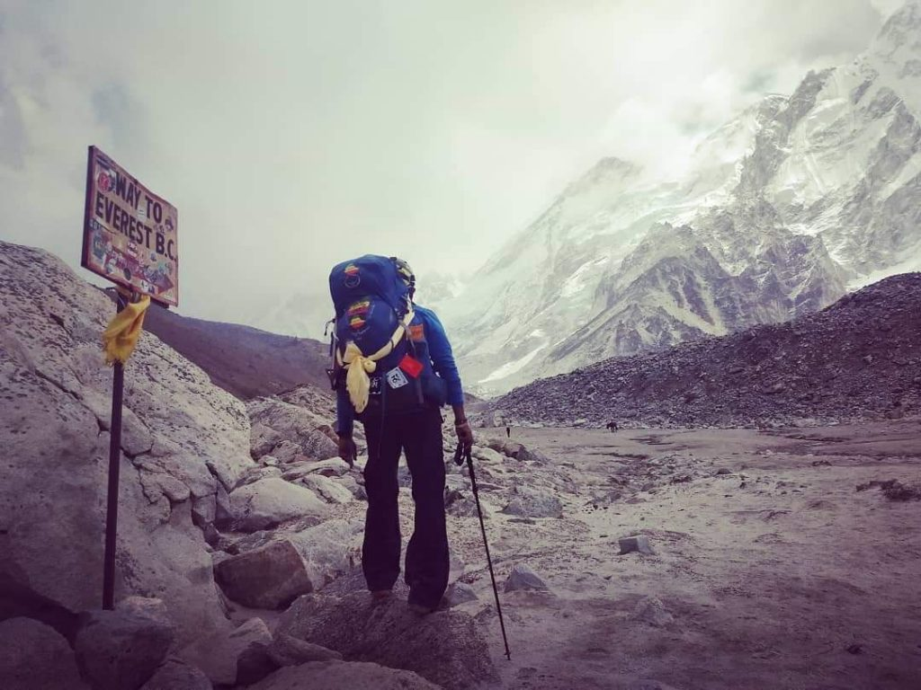 "Sirak stands with backpack at Gorakshep, a small Himalayan Village at an elevation of about 16,942 ft. Note the iconic sign, ""Way to Everest Base Camp""."
