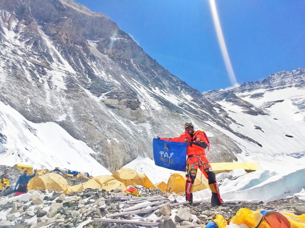 Seyoum at Camp 2 holding up a big blue flag that says Walia prior to heading up to Camp 3, and higher. Walia beer, a product of Heineken primarily sold in Ethiopia, was one of Seyoum's climbing sponsors.
