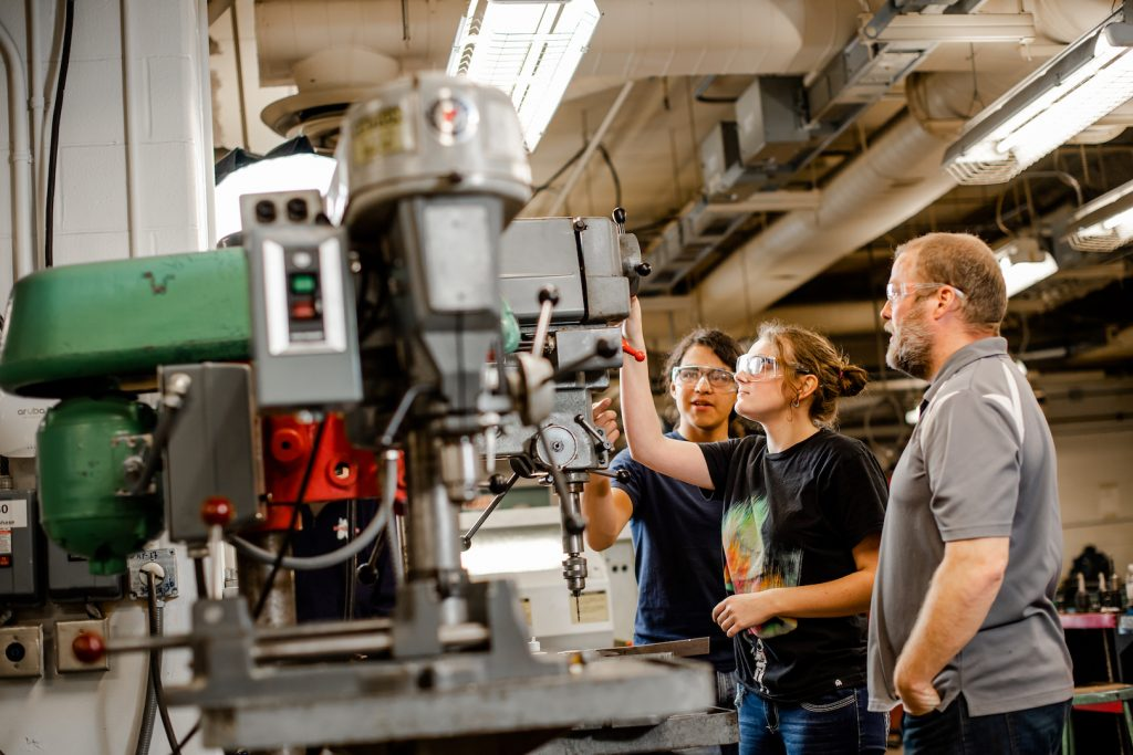 The Department of Manufacturing and Mechanical Engineering Technology maintains a machine shop with comprehensive facilities available to Michigan Tech students. The shop also offers machining and fabrication services for the university research community. Students and a faculty member examine a large drill in the machine shop.