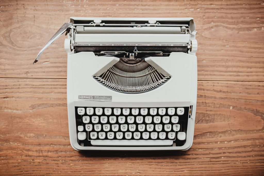 Photo of white old fashioned typewriter on an old wooden desk or tabletop.