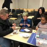 "Matt Friiswall and his children Iziah and Isabel work on designing a scoop to remove trash from the ""pond""."
