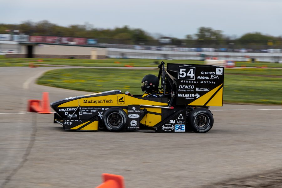 F-276 Racecar racing by on a speedway with the driver shown in his black helmet.