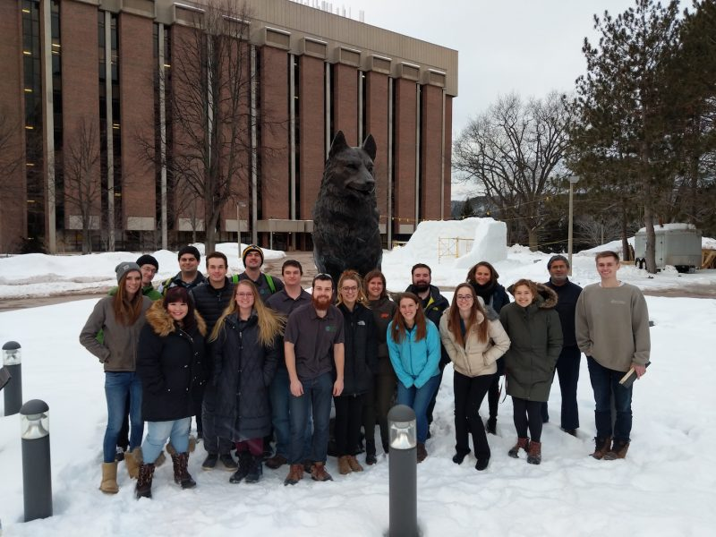 Team photo near the Husky statue at Michigan Tech, in the snow.