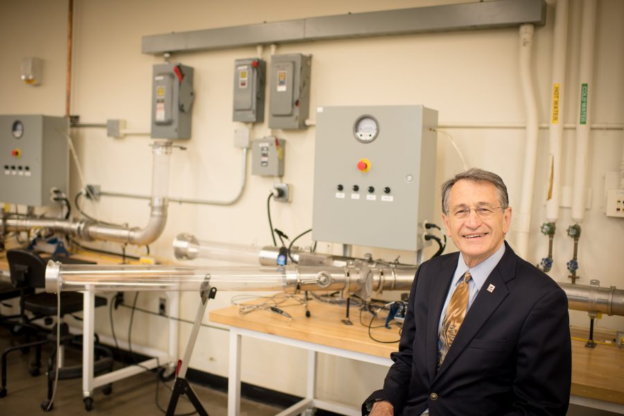 ME-EM Department Chair Bill Predebon stands in an empty lab classroom in the R.L. Smith Building on campus, with some equipment in the backround.
