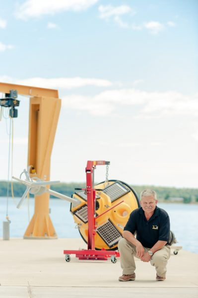 Guy Meadows on the dock of the Great Lakes Research Center at Michigan Tech, in front of a large, bright yellow buoy (about the size of a very small compact car) that is used to collect data in Lake Superior.