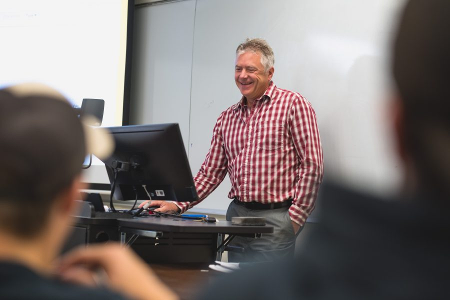 John Irwin stands at the front of a class with white board in the background. He wears a red and white checked shirt, and he is smiling at the class.