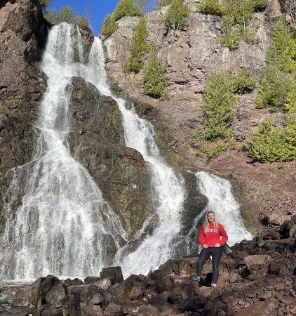 Amanda stands by a huge waterfall