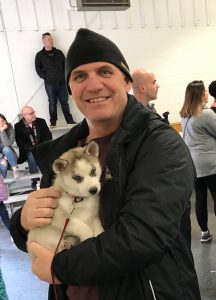 Coach Shawhan holds a tiny Husky pup in his arms.