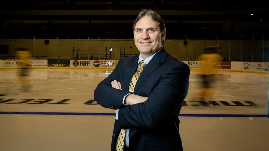 Coach Joe Shawhan stands with arms folded with ice rink in the background.