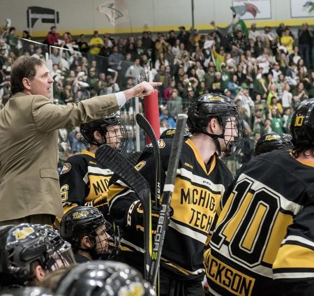 Coach Shawhan points with his arm extended over the heads of his hockey players at the sidelines during a hockey game.