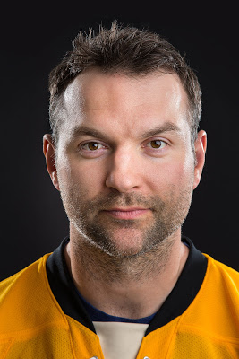 Head shot of John Scott wearing his gold MTU hockey jersey.