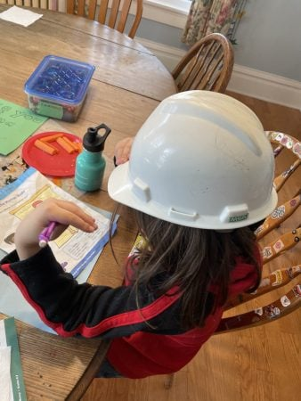 younger child at kitchen table wearing white hard hat