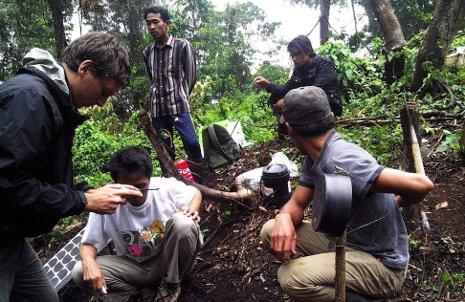 Jay Wellik, left, installs a new seismometer near Raung volcano.