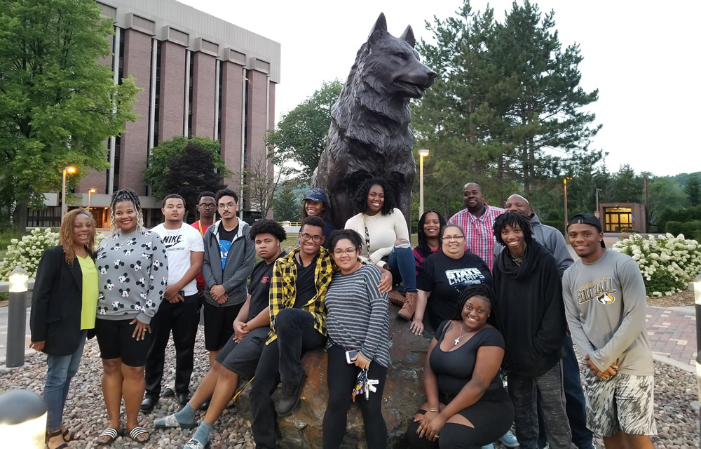 Students at the Husky statue during their visit to campus.