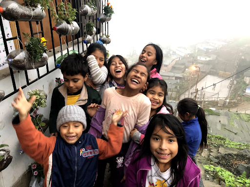 A group of elementary school-aged children in Peru, standing next to planters made of two liter soda bottles.