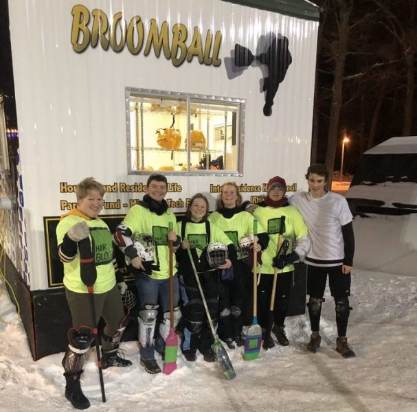 Students in matching jerseys hold broomball sticks in front of a food trailer