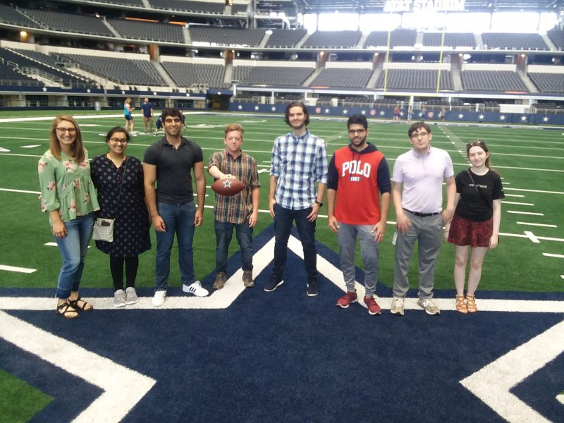 A group of college students stands on the star decal at center field of AT&T stadium