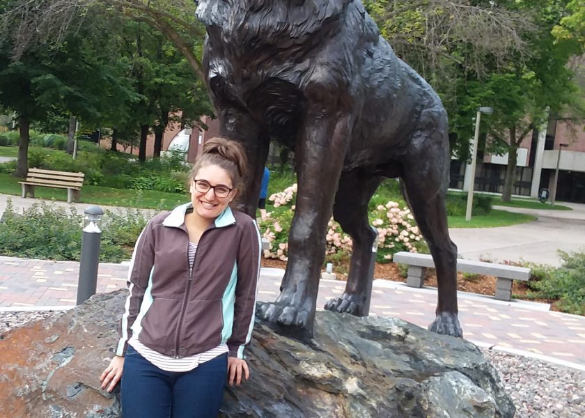 A young woman sitting on the base of the Michigan Tech husky statue and smiling.