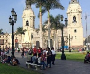 People standing in front of a large temple on a city street in Lima, Peru