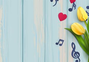 Music notes and yellow tulips on blue wooden background.