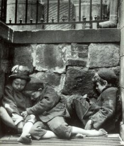 Black and white photo of three children sleeping on the street.