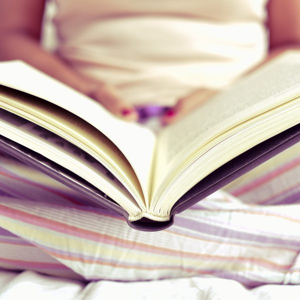 closeup of a young caucasian woman in pajamas reading a book in bed