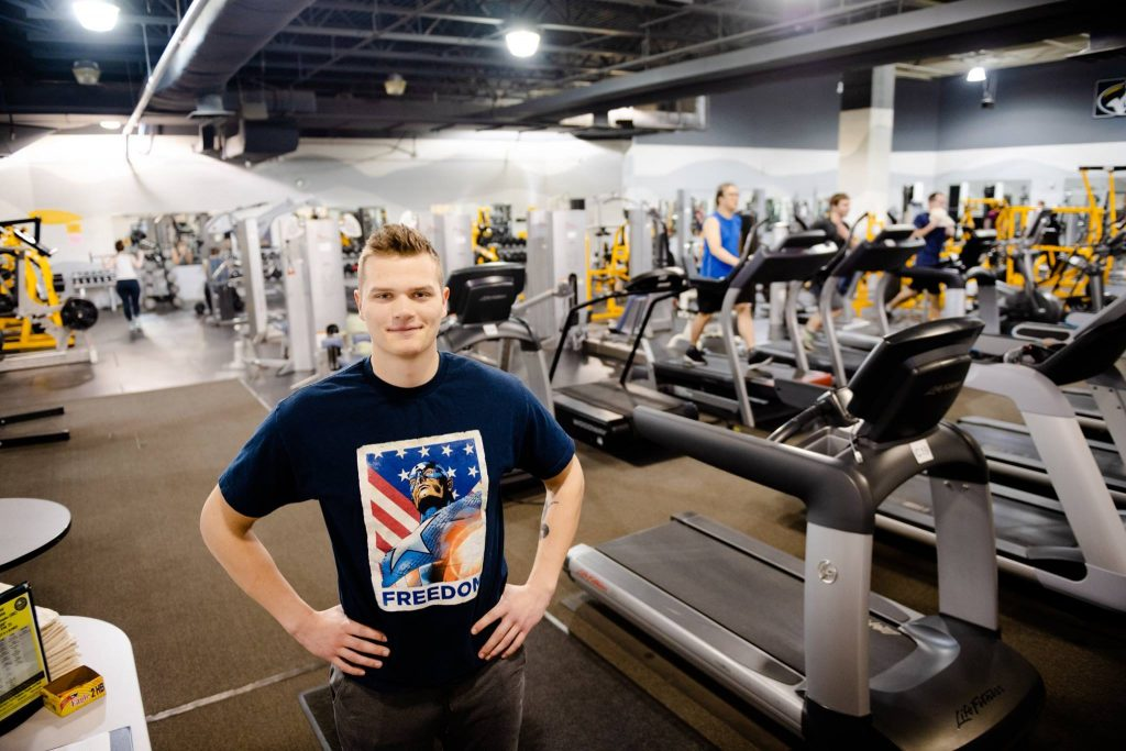 A young man in a Captain America shirt stands in a fitness center.