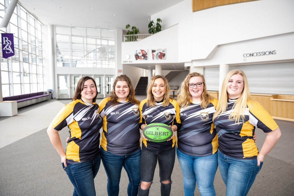 Five women in rugby shirts pose for a group photo.
