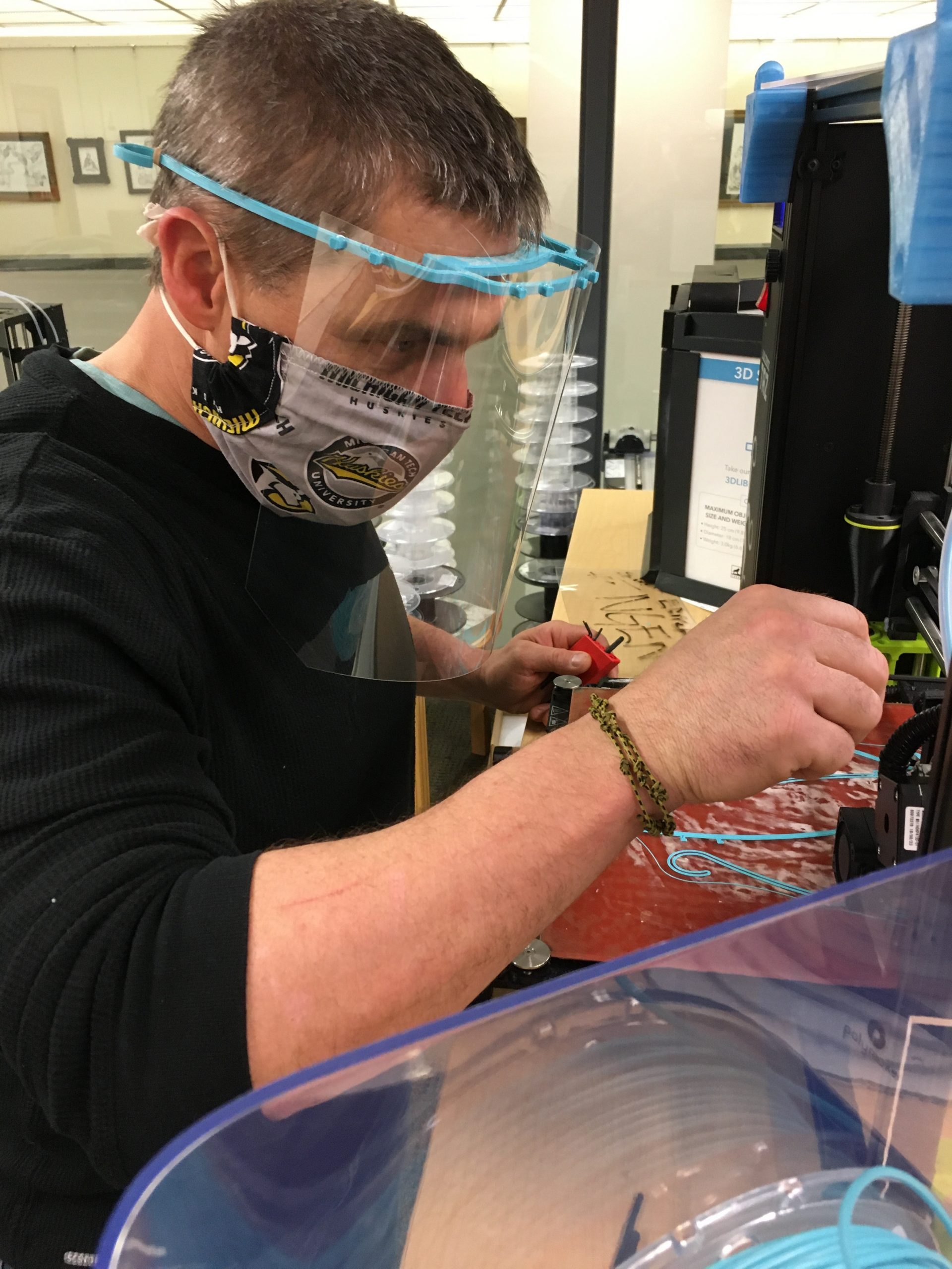 A man wearing a Michigan Tech Huskies face mask and a plastic shield working at a 3D printer in a library.
