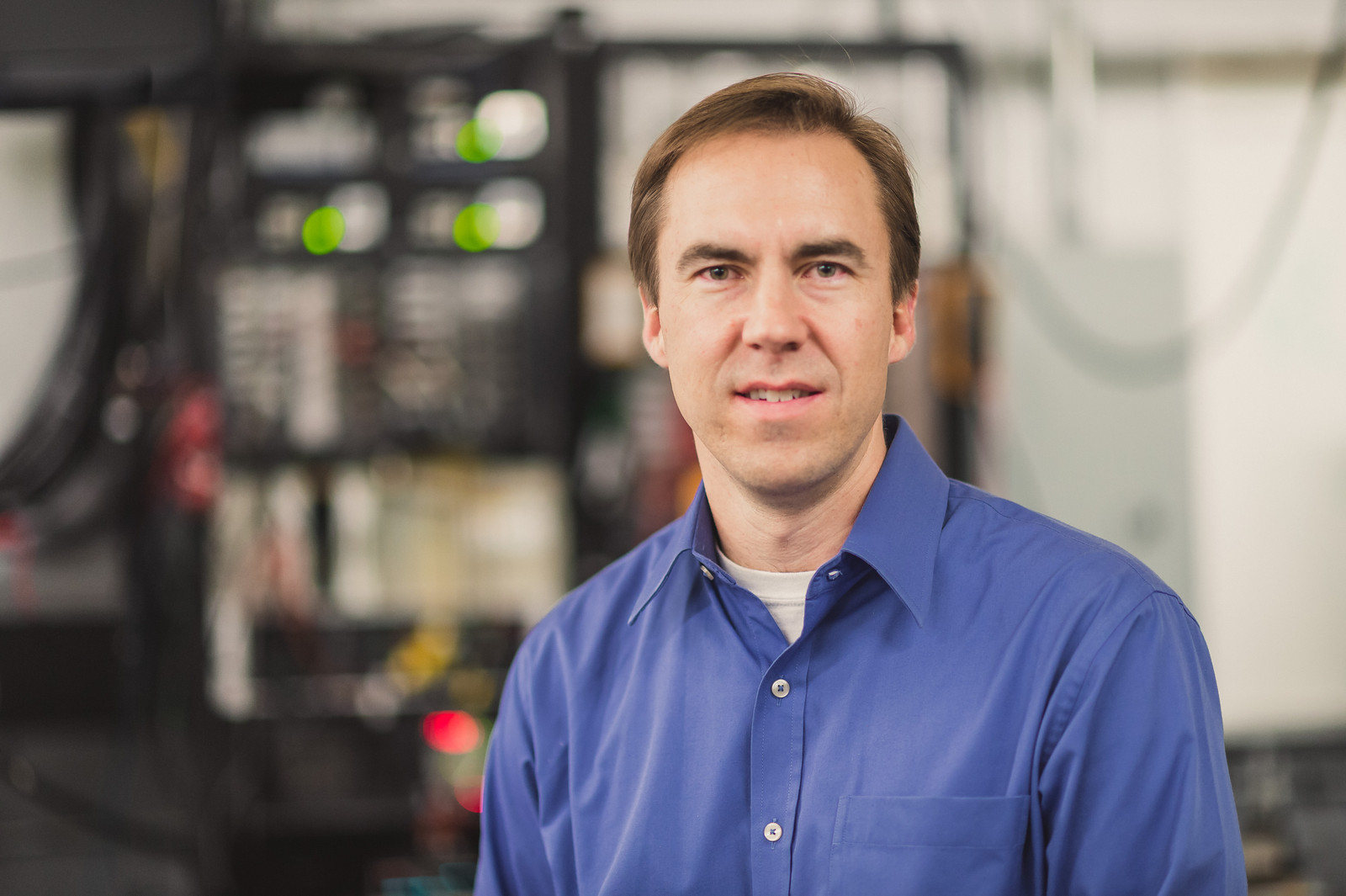 A man in a blue shirt with blurred background of equipment in a mechanical engineering aerospace lab smiles at the camera.