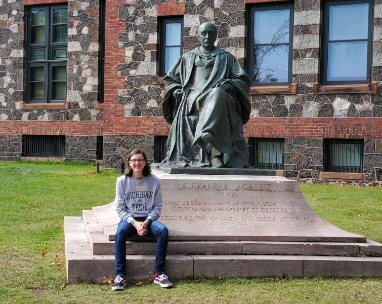 A young woman in a Michigan Tech sweatshirt sits by a statue of Alexander Agassiz in Calumet Michigan outside