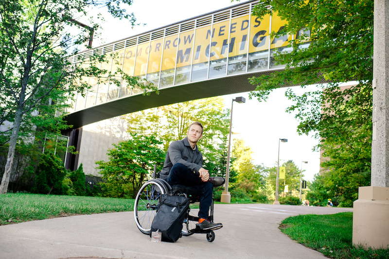 A young man sitting in a wheelchair with his backpack on a sidewalk with Tomorrow Needs Michigan Tech on the banner behind him