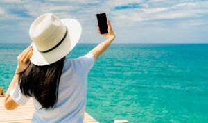 Young Asian woman wear straw hat in casual style use smartphone taking selfie