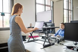 Business woman working on laptop computer at ergonomic standing desk. Female professional working at her desk with male colleague working at the back.
