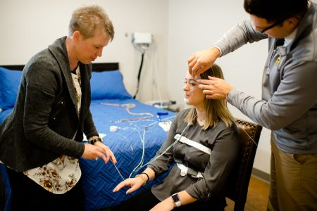 Two researchers setting up a participant for a sleep study