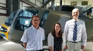 Enstrom employees in front of a helicopter
