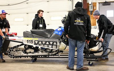 Michigan Tech students standing by their snowmobile.