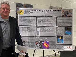 John Irwin standing by a poster.