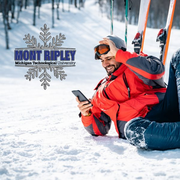 Smiling male skier sitting on snow taking a break while using phone. Mont Ripley logo.