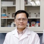 Yoke Kin Yap in a lab with lab coat and safety glasses