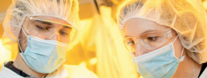Two researchers in masks, safety glasses, and hair covering