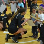 Stephanie Dietrich kneeling after a basketball game to young children