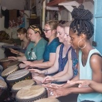 In a row, Americans and Ghanians play hand drums at a cultural event.