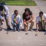 Students race solar powered cars as part of a challenge in the renewable energy course.