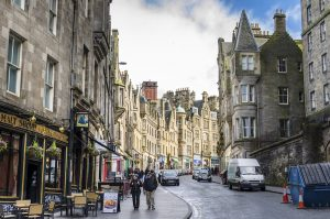 Edinburg, UK - March 28, 2015: Locals and Tourists Strolling along Cockburn Street in Old Town on a cloudy winter day. Cockburn Street is a picturesque street created as a serpentine link from the Royal Mile to Waverley Station in 1856 in Edinburgh's city centre.