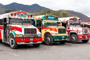 "Antigua - Guatemala - January 24, 2013: Traditional Guatemalan local ""Chicken Bus"" station in Antigua, Guatemala. It is located behind the busy street market in Antigua."